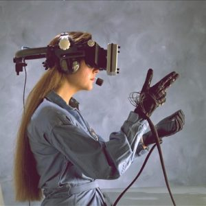 A woman wearing virtual reality helmet and a glove